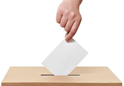 A hand placing a ballot in a box